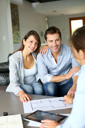 architects: Couple meeting architect for plans of future home Stock Photo