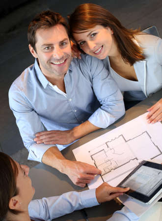 building plans: Couple meeting architect for plans of future home Stock Photo