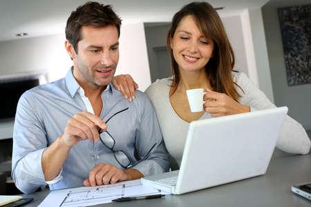 real man: Couple at home looking at future home blueprint