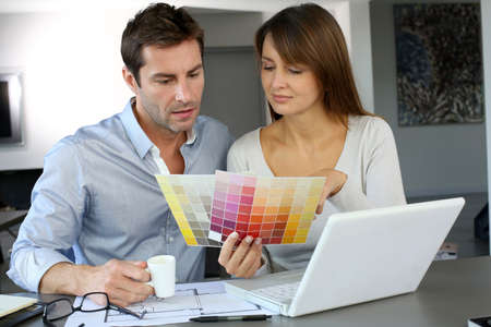 choosing: Couple choosing paint colour for their new home