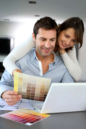 Couple choosing paint colour for their new home photo