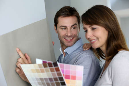 Couple choosing paperwall colour for their new home Stock Photo - 15831997
