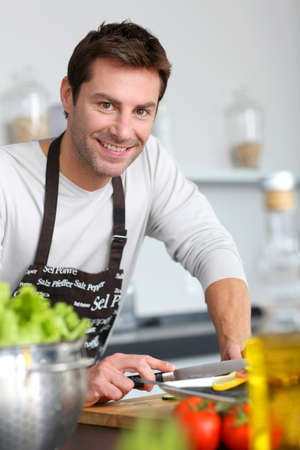 Man in kitchen preparing dinner photo