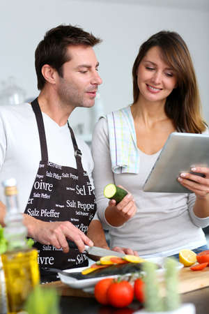 Couple in home kitchen using electronic tablet photo