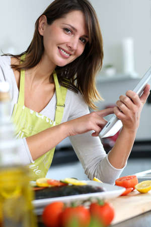 Woman in kitchen looking for dish recipe on internet photo