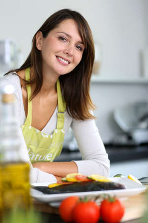 Smiling brunette woman in home kitchen photo