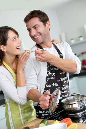 Man preparing dinner and making her wife taste the food photo