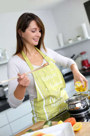 Woman in kitchen preparing pasta dish photo