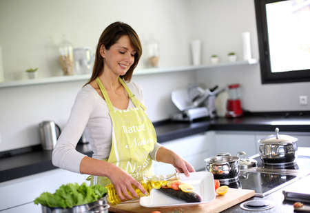 Woman in kitchen preparing fish dish photo