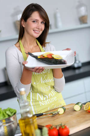 Woman in kitchen holding fish dish photo