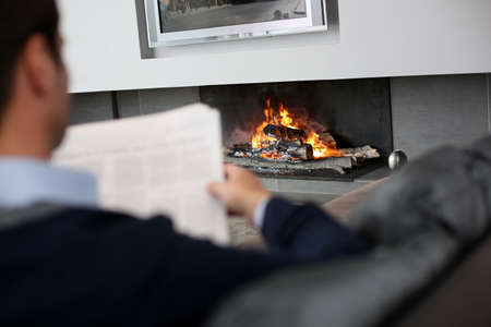 Man at home reading newspaper in front of fireplace Stock Photo - 15831894