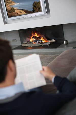 Man at home reading newspaper in front of fireplace Stock Photo - 15831901