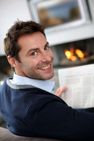 Man at home reading newspaper in front of fireplace Stock Photo - 15831946
