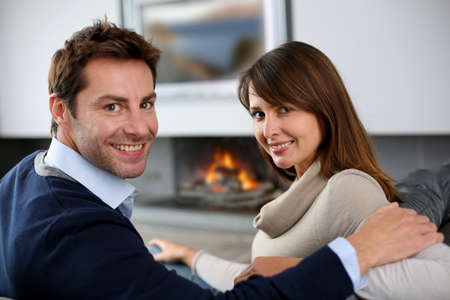 Romantic couple sitting by fireplace at home photo