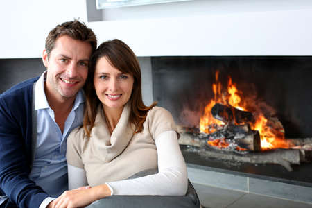 winter wedding: Romantic couple sitting by fireplace at home Stock Photo