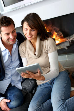 Couple sitting by fireplace and websurfing with tablet Zdjęcie Seryjne
