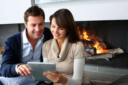 Couple sitting by fireplace and websurfing with tablet photo