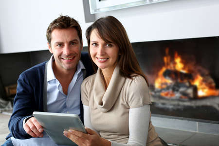 married couples: Couple sitting by fireplace and websurfing with tablet Stock Photo