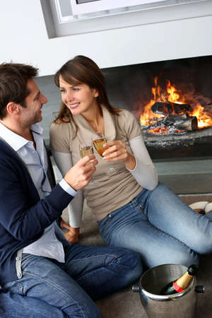 Cheerful couple drinking champaign by fireplace photo