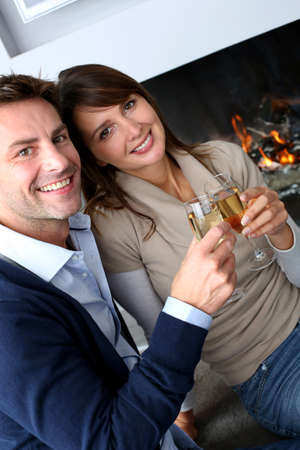 champaign: Cheerful couple drinking champaign by fireplace