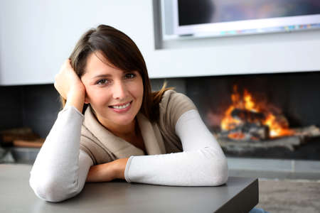 Beautiful woman sitting by fireplace at home photo