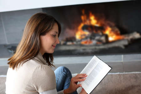 Portrait of beautiful woman reading book by fireplace Stock Photo - 15831939