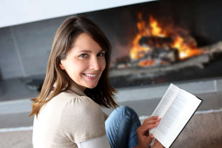 fireplace home: Portrait of beautiful woman reading book by fireplace