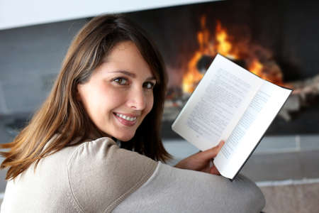 quiet adult: Portrait of beautiful woman reading book by fireplace