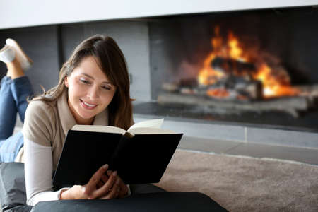 comfortable: Portrait of beautiful woman reading book by fireplace