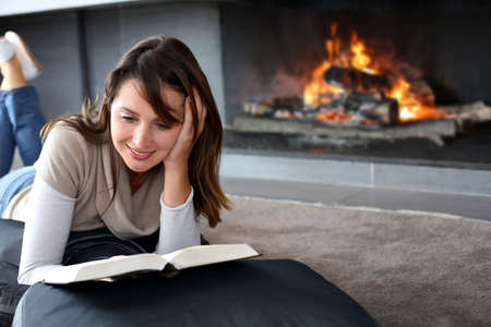 Portrait of beautiful woman reading book by fireplace Stock Photo - 15831919