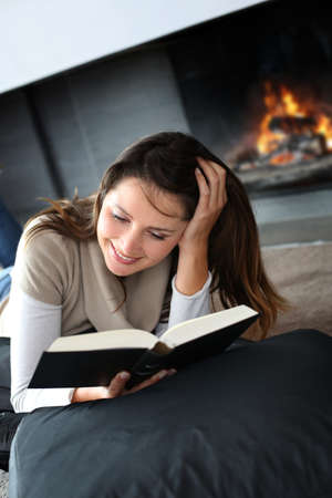 Portrait of beautiful woman reading book by fireplace photo