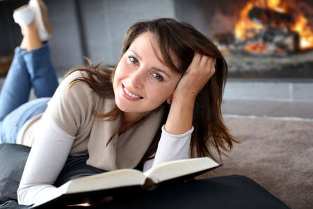 home comfort: Portrait of beautiful woman reading book by fireplace