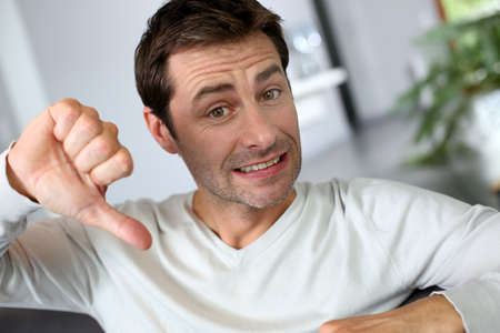 Discontented man showing thumb down photo