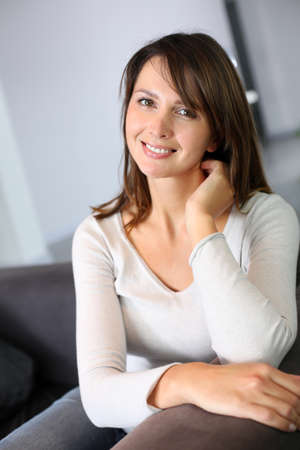 Attractive woman sitting in sofa at home Stock Photo - 15831935