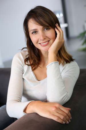 Attractive woman sitting in sofa at home Stock Photo - 15831951