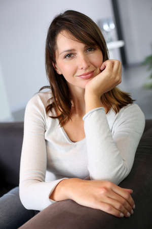 Attractive woman sitting in sofa at home photo