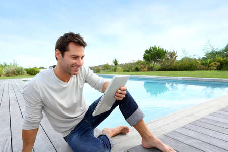 Man sitting by pool with digital tablet Stock Photo - 15849385