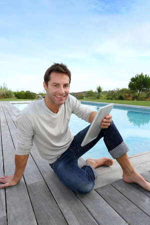 Man sitting by pool with digital tablet photo