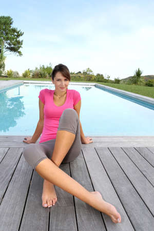 Woman sitting by pool after exercising photo