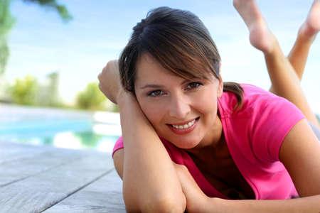 Chica alegre que pone en el recinto de la piscina después de hacer ejercicio