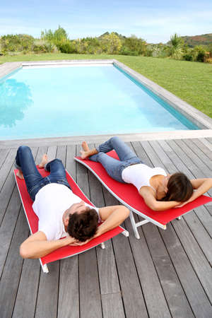 pool deck: Couple relaxing in long chairs by outdoor pool