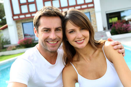 happy old man: Cheerful couple sitting in front of new house