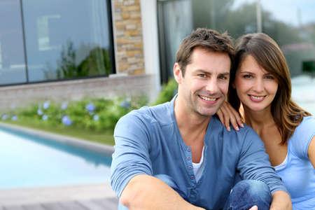 pareja en casa: Pareja alegre que se sienta delante de la nueva casa