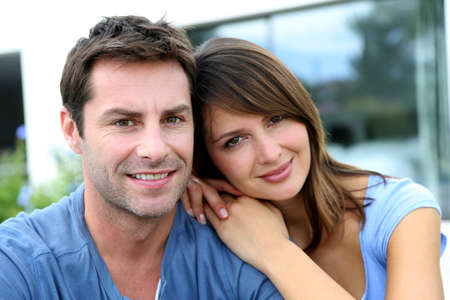 wives: Cheerful couple sitting in front of new house