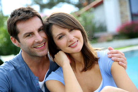 Cheerful couple sitting in front of new house photo