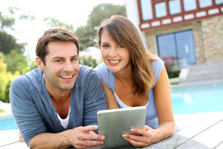 Couple websurfing on internet with tablet photo
