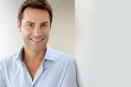 Portret van knappe en gelukkige man leunend op muur Stockfoto