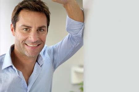 bel homme: Portrait de beau mec et heureux penchant sur le mur
