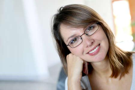 wearing spectacles: Smiling brunette woman wearing eyeglasses