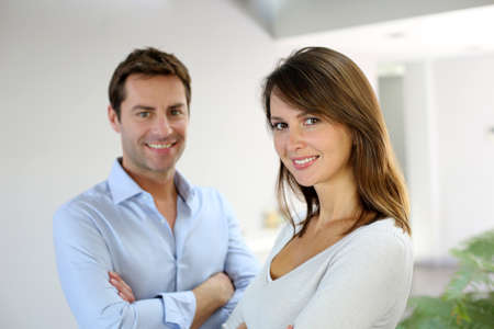 Portrait of married couple standing with arms crossed photo